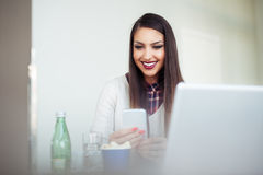 Freelance young woman sitting in the cafeteria with laptop and using mobile phone Stock Images