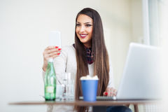 Freelance young woman sitting in the cafeteria with laptop and using mobile phone Stock Image