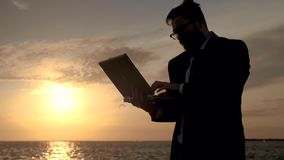 Freelancer με ένα lap-top στη μέση της θάλασσας στο υπόβαθρο ενός θαυμάσιου ηλιοβασιλέματος απόθεμα βίντεο