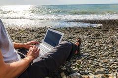 Freelancer που λειτουργεί με ένα lap-top στην παραλία Στοκ φωτογραφία με δικαίωμα ελεύθερης χρήσης