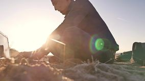 freelancer Силуэт человека работая на фрилансере компьтер-книжки сидя на солнце слепимости солнца захода солнца песка Стоковые Изображения