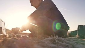 freelancer Силуэт человека работая на фрилансере компьтер-книжки сидя на солнце слепимости солнца захода солнца песка Стоковые Фотографии RF