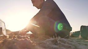 freelancer Силуэт человека работая на фрилансере компьтер-книжки сидя на солнце слепимости солнца захода солнца песка Стоковое Фото