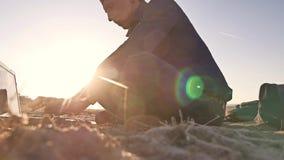 freelancer Силуэт человека работая на фрилансере компьтер-книжки сидя на солнце слепимости солнца захода солнца песка Стоковые Изображения RF