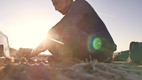 freelancer Силуэт человека работая на фрилансере компьтер-книжки сидя на солнце слепимости солнца захода солнца песка Стоковые Фото