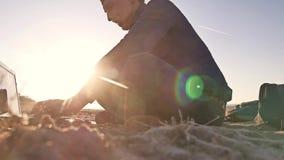 freelancer Силуэт человека работая на фрилансере компьтер-книжки сидя на солнце слепимости солнца захода солнца песка Стоковое фото RF