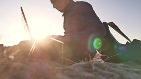 freelancer Человек работая на фрилансере компьтер-книжки сидя на силуэте солнца слепимости солнца захода солнца песка Стоковая Фотография RF