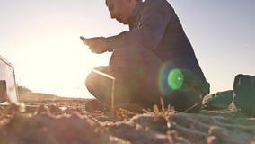 freelancer Человек работая на фрилансере компьтер-книжки сидя на силуэте солнца слепимости солнца захода солнца песка Стоковые Изображения RF