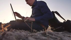 freelancer Человек работая на фрилансере компьтер-книжки сидя на силуэте солнца слепимости солнца захода солнца песка Стоковое Изображение