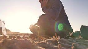 freelancer Человек работая на фрилансере компьтер-книжки сидя на силуэте солнца слепимости солнца захода солнца песка Стоковая Фотография