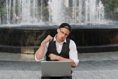 Freelancer acertado feliz que trabaja con el ordenador portátil al aire libre Fotos de archivo