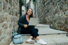 Freelancer adulto hermoso en la rebeca azul marino que trabaja en lapt fotografía de archivo libre de regalías