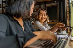 Freelancer asiático feliz das mulheres que tem a discussão e que trabalha no portátil fotos de stock royalty free