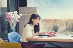 Freelancer asiático que trabalha no portátil do computador contra o escritório urbano Fotografia de Stock Royalty Free