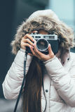 Freelancer asian photographer exploring in cold weather. Young photographer in winter coat Royalty Free Stock Photos