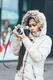 Freelancer asian photographer exploring in cold weather. Young photographer in winter coat Royalty Free Stock Photography