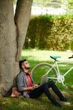Freelancer barbudo que trabaja en el parque público imágenes de archivo libres de regalías