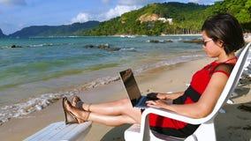 Freelancer bastante asiático de la mujer que trabaja en la playa tropical almacen de video