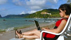 Freelancer bastante asiático de la mujer que trabaja en la playa tropical hermosa almacen de metraje de vídeo