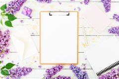 Freelancer or blogger concept. Minimalistic workspace with clipboard, envelope, pen, box, lilac and accessories on white backgroun. D. Flat lay Stock Image