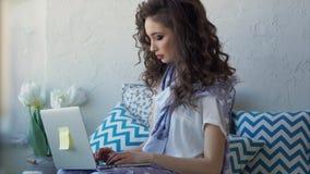 Freelancer bonito joven de la mujer que trabaja con su ordenador portátil en casa en el dormitorio almacen de metraje de vídeo
