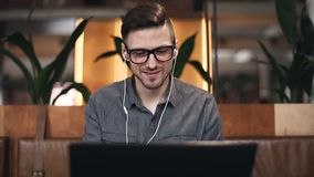 Freelancer Browsing at His Laptop. Attractive freelancer man in the glasses and headphones wearing casual outfit enjoying his favorite songs and singing it while stock video