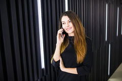 Freelancer business woman talking on the mobile phone with office room in the background. Freelancer business woman talking on the mobile phone with office Stock Photos