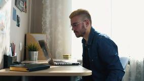 Freelancer casero joven hermoso con los vidrios y el pelo amarillo que trabajan en casa, usando un ordenador portátil Mientras qu metrajes