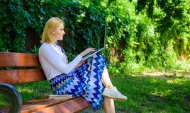 Freelancer da senhora que trabalha no parque Benefícios autônomos A mulher com portátil trabalha o fundo exterior, verde da natur fotografia de stock royalty free
