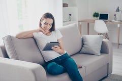 Freelancer de cabelo marrom lindo de refrigeração no sofá bege em fotos de stock royalty free