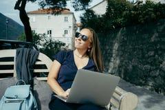 Freelancer de la mujer joven en las gafas de sol que trabajan con el ordenador portátil en outd fotos de archivo libres de regalías