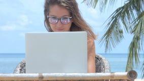 Freelancer de la mujer joven que trabaja en ordenador portátil en la playa Trabaja independientemente el trabajo, 6 tiros metrajes