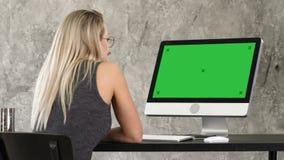 Freelancer de la mujer que mira el monitor de computadora Exhibición verde de la maqueta de la pantalla almacen de video