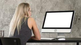Freelancer de la mujer que mira el monitor de computadora Visualización blanca almacen de metraje de vídeo