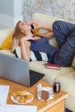Freelancer de sexo femenino en su ropa casera casual que trabaja remotly de su mesa de comedor por la mañana Casas en un sofá enc Fotos de archivo