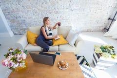 Freelancer de sexo femenino en su ropa casera casual que trabaja remotly de su mesa de comedor por la mañana Casas en un sofá enc Fotografía de archivo libre de regalías