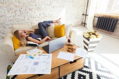Freelancer de sexo femenino en su ropa casera casual que trabaja remotly de su mesa de comedor por la mañana Casas en un sofá enc Fotografía de archivo