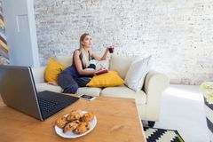 Freelancer de sexo femenino en su ropa casera casual que trabaja remotly de su mesa de comedor por la mañana Casas en un sofá enc Imagen de archivo