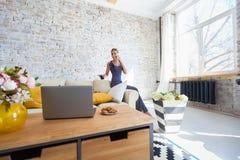 Freelancer de sexo femenino en su ropa casera casual que trabaja remotly de su mesa de comedor por la mañana Casas en un sofá enc Foto de archivo libre de regalías