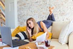 Freelancer de sexo femenino en su ropa casera casual que trabaja remotly de su mesa de comedor por la mañana Casas en un sofá enc Imagenes de archivo