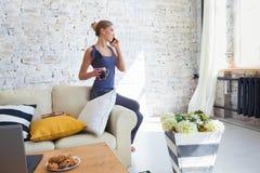 Freelancer de sexo femenino en su ropa casera casual que trabaja remotly de su mesa de comedor por la mañana Casas en un sofá enc Imagen de archivo libre de regalías