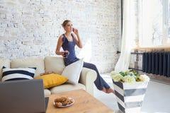 Freelancer de sexo femenino en su ropa casera casual que trabaja remotly de su mesa de comedor por la mañana Casas en un sofá enc Imágenes de archivo libres de regalías