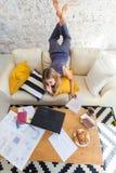 Freelancer de sexo femenino en su ropa casera casual que trabaja remotly de su mesa de comedor por la mañana Casas en un sofá enc Fotos de archivo libres de regalías