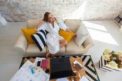Freelancer de sexo femenino en una ropa blanca de la capa que trabaja remotly de su mesa de comedor por la mañana Casas en un sof Imágenes de archivo libres de regalías