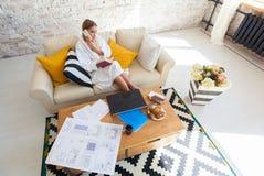 Freelancer de sexo femenino en una ropa blanca de la capa que trabaja remotly de su mesa de comedor por la mañana Casas en un sof Imagen de archivo libre de regalías