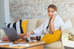 Freelancer de sexo femenino en una ropa blanca de la capa que trabaja remotly de su mesa de comedor por la mañana Casas en un sof Imagenes de archivo