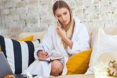 Freelancer de sexo femenino en una ropa blanca de la capa que trabaja remotly de su mesa de comedor por la mañana Casas en un sof Fotografía de archivo libre de regalías