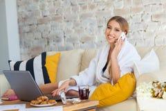 Freelancer de sexo femenino en una ropa blanca de la capa que trabaja remotly de su mesa de comedor por la mañana Casas en un sof Fotografía de archivo