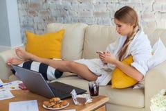 Freelancer de sexo femenino en una ropa blanca de la capa que trabaja remotly de su mesa de comedor por la mañana Casas en un sof Foto de archivo libre de regalías