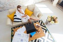 Freelancer de sexo femenino en una ropa blanca de la capa que trabaja remotly de su mesa de comedor por la mañana Casas en un sof Fotos de archivo libres de regalías